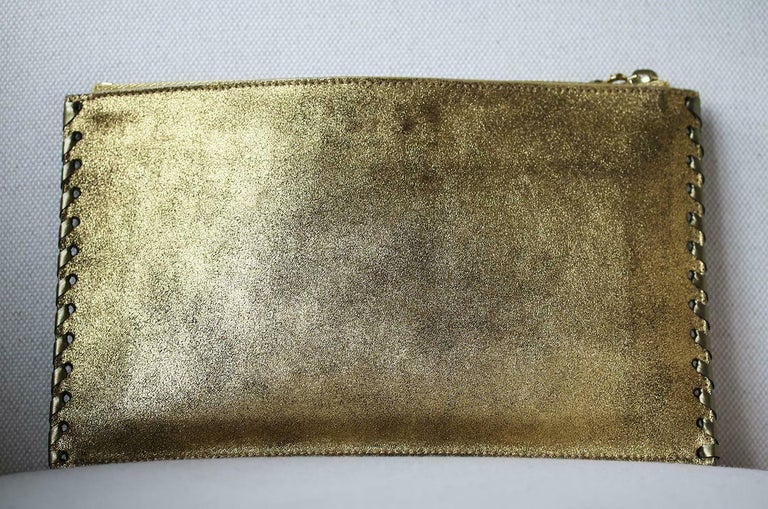 Balmain master of all things fabulously glamorous never fails to deliver. This crystal embellished soft suede pouch with top zipper fastening is the perfect summer accessory. Crafted from burnished gold soft suede and finished with a top layer of