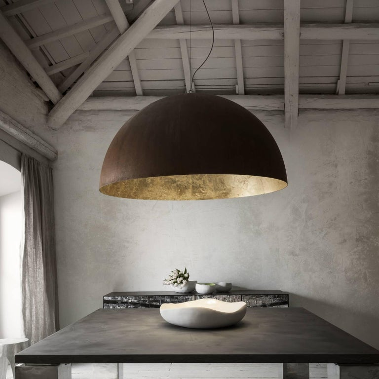 Crafted of metal with a Corten finish, the interior of the semicircular shade is decorated with delicate gold leaf.
