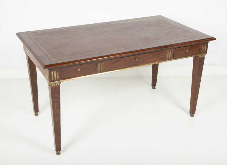 A Baltic mahogany leather top and brass fluted writing table with three frieze drawers on square bronze mounted tapering legs.