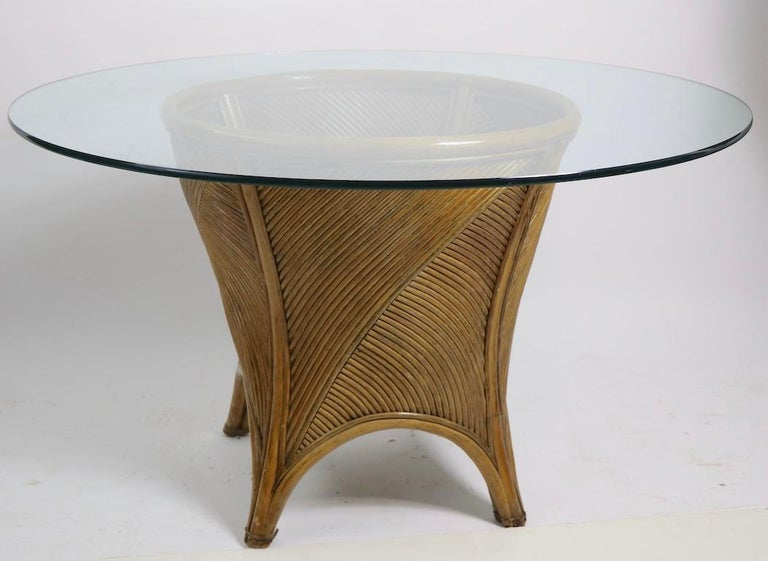 Chic and stylish glass top, bamboo base dining table, in the style of McGuire Furniture. The center pedestal base (20 W x 20 D x 28 Dia. inch) supports a thick (.50 in.) circular glass disk top (48 Dia. in.). Tghis example is in very good original