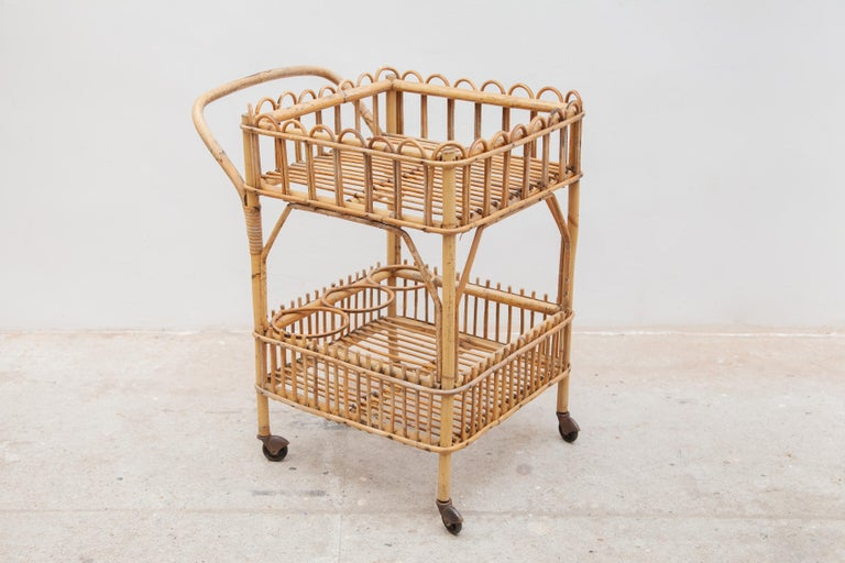 A very nice and decorative bamboo bar cart, serving trolley designed in the 50s Italy, storage for 3 bottles. In original good condition.