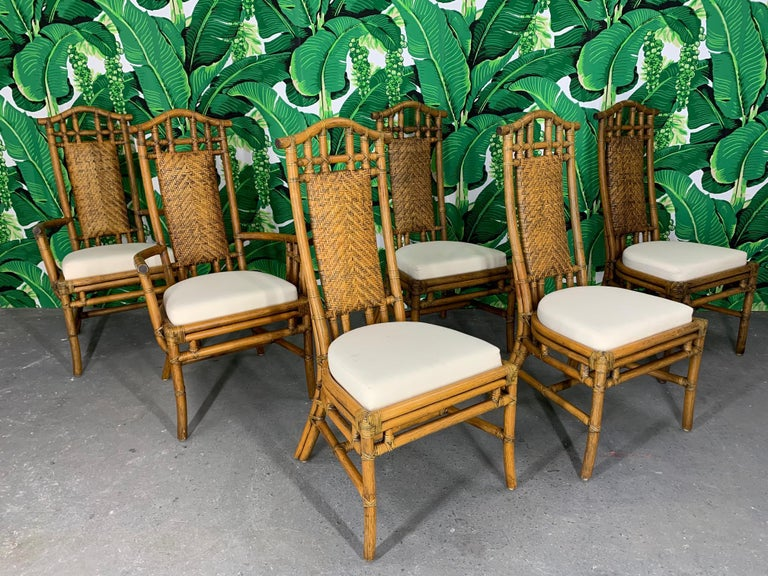 McGuire rattan pagoda high back dining chairs and matching dining table feature woven rattan cushioned chair backs and upholstered seats. Very good condition with minor imperfections consistent with age. Some light staining on seats.