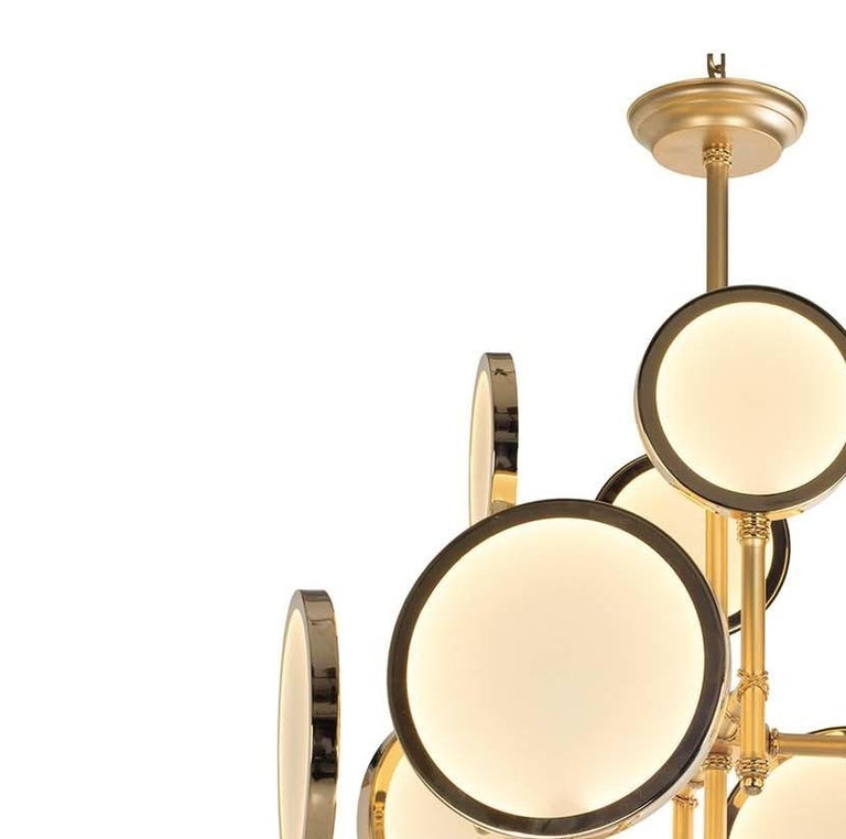 This captivating chandelier reinterprets traditional light fixtures with a contemporary edge to create a timeless objet d'art that will complement any decor. The linear frame, fashioned of brass with a satin gold finish, features a central rod