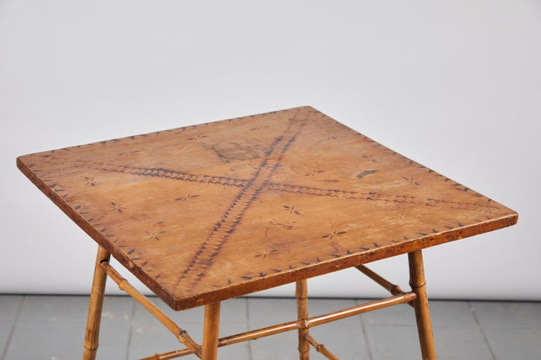 Bamboo side table with wooden top with darkened stenciled details.
