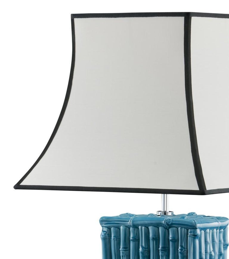 The ceramic stand of this striking lamp reproduces a structure made of bamboo sticks with a vivid turquoise color. The elegant white shade is accented with black giving the piece an elegant finish.