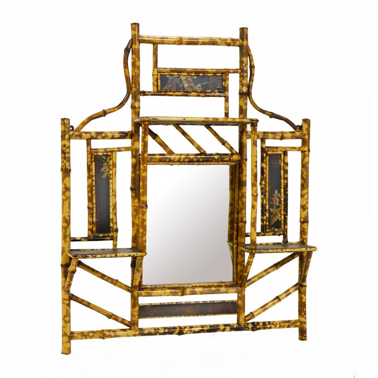 A delightful piece which is equally at home in an Asian modern interior as it is in a tropical space, this antiqued bamboo wall shelf has a mirror as its focal point. It is surrounded by 4 shelves and 4 infil panels of decorated metal (presumably