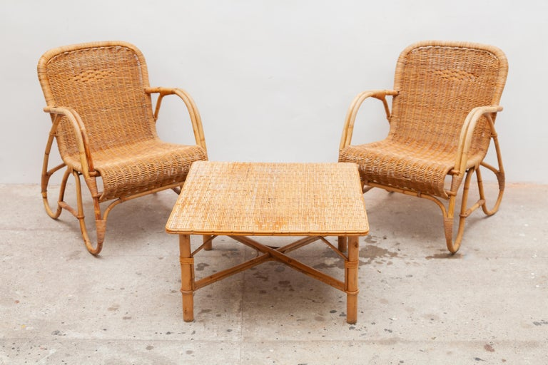 Vintage midcentury bamboo lounge chairs and table set. Woven rattan seats and tabletop. Dimensions: Chairs 55 W x 72 H x 70 D cm, seat 35cm high, table 65 W x 37 H x 65 D cm.