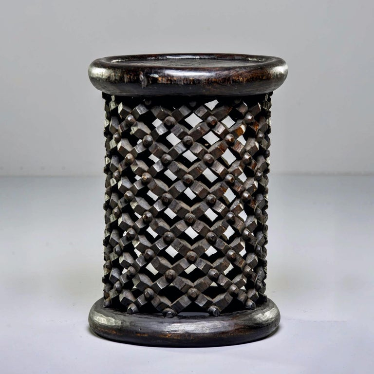This circa 1980s hand carved narrow pedestal style stool or side table was made from a single piece of wood by the Bamileke people of Cameroon. The intricate knobby carved lattice work of the base symbolizes life's webs that bind us together. Sold