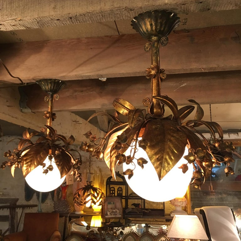 Beautiful pair of Banci Firenze gilt globe pendant lights,  Italy,  1950s  Gilt leaves and flowers surround a 15cm milk glass globe  Twisted decorative details form the stem along with more flowers  The lights are fixed to scalloped