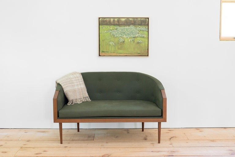 A new iteration which echoes that of our chairs of the same name, the loveseat, shown here in walnut with green cotton upholstery and two rows of button tufting, uses an elongated barrel form to cradle the body. Four hand-turned and tapered legs