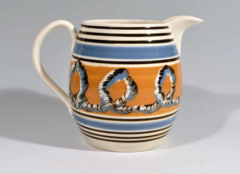 Banded pearlware mocha jug with Earthworm design,  1790-1810.  The barrow-form jug has a wide central band of ochre decorated with a three-color earthworm design. Above and below are a series of line in blue and brown. The loop handle with leaf