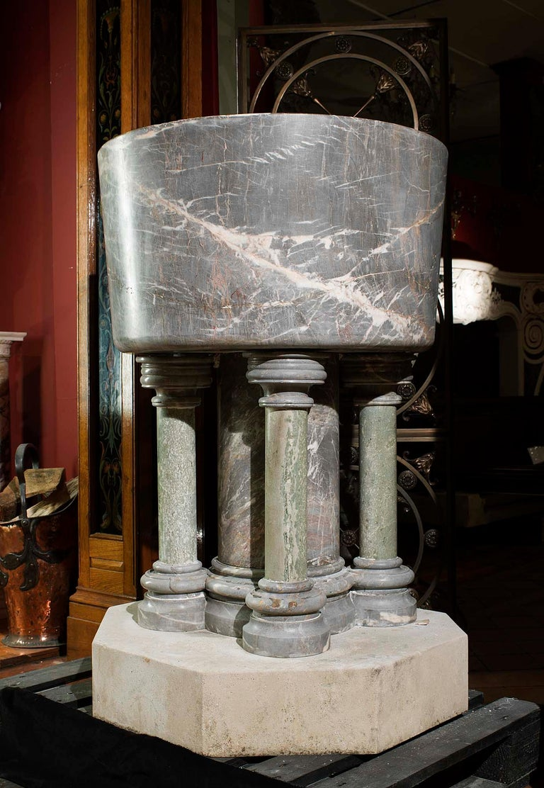 An impressive and large baptismal font entirely carved from Ashburton Marble. This is a soft grey and blush pink, lightly veined marble with evidence of fossil remains of creatures, principally corals, crinoids and brachiopods, that lived in the