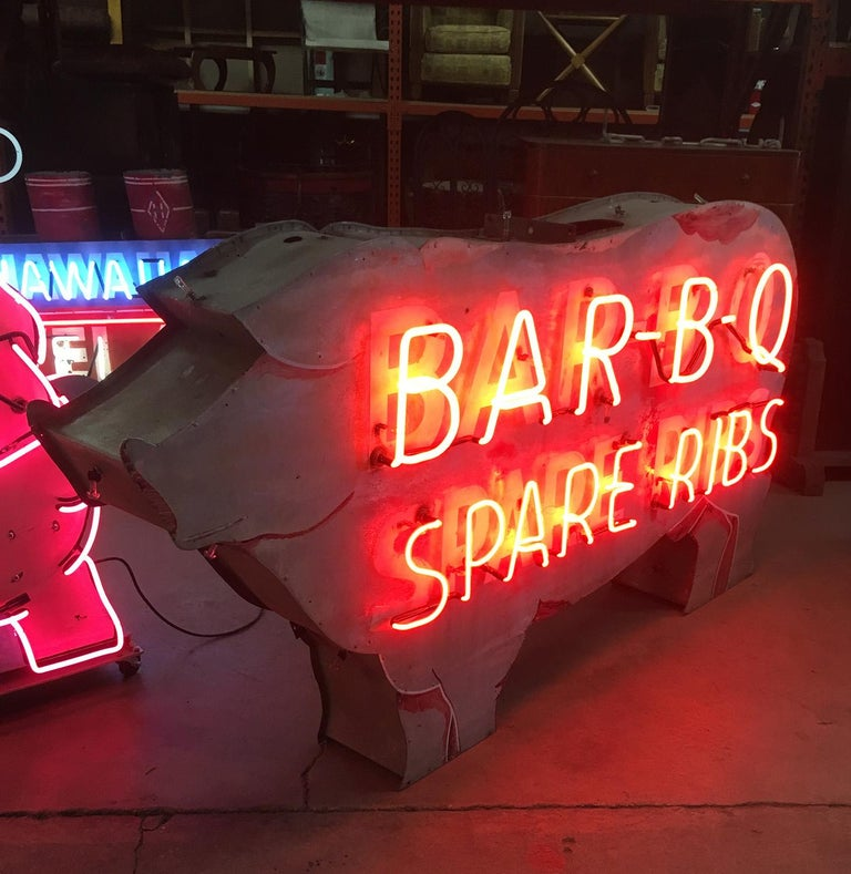 This fantastic neon sign once graced the front of a Bar - B - Q restaurant, and features its' pork spare ribs. The painted metal sign is double sided, and could have neon added to the reverse side, as well as a trim of neon around the pigs body (at