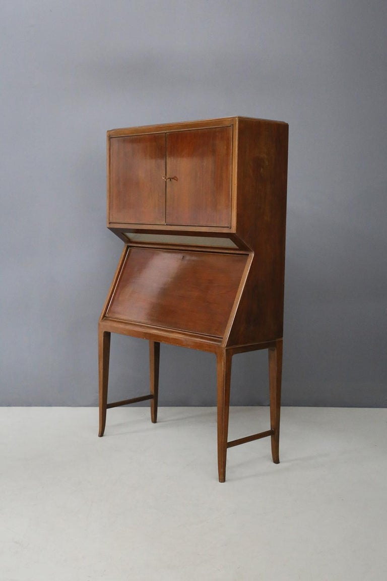 Folding bar cabinet, Italian manufacture of the 1950s. Beautiful Italian walnut and maple of the 1950s. A piece of furniture made up of many distinctive elements for its different uses. In the first upper part of the cabinet there are two opening