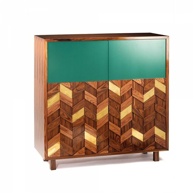 Samoa bar cabinet is a high quality product by Mambo Unlimited Ideas, crafted in polished or matte wood veneer structure and feet, brass applications and lacquered doors. It features a three dimensional design on its doors, elegant polished brass