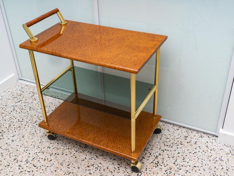This stylish and chic Italian bar cart dates to the 1970s and is fabricated in Karelian birchwood veneer and gold-plated hardware. The piece makes a subtle and luxurious statement with it clean lines and use of materials.