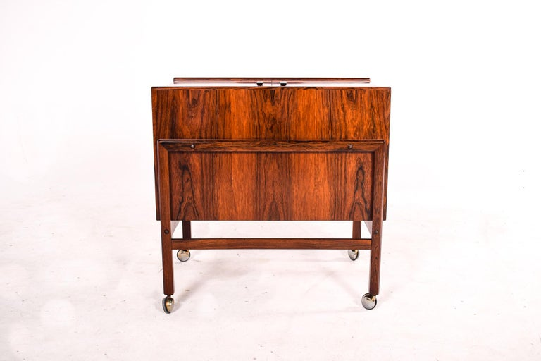 Danish design at its best. Bar cart in rosewood by Andreas Hansen for Arrebo Mobler in the 1960's. The top opens out to reveal a fantastic bar space, complete with serving shelves and a bottle rack. Supported on casters for easier movement.