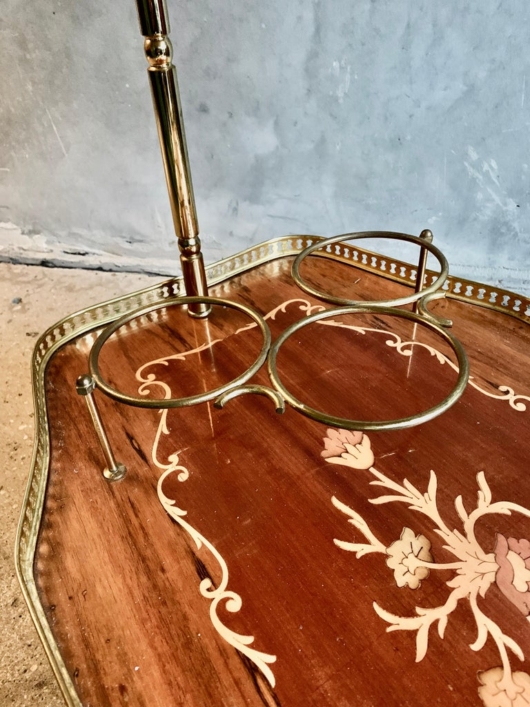 Lovely Italian bar cart trolley midcentury featuring one veneered tray, a glass tray and four bottle holders brass, 1950s.