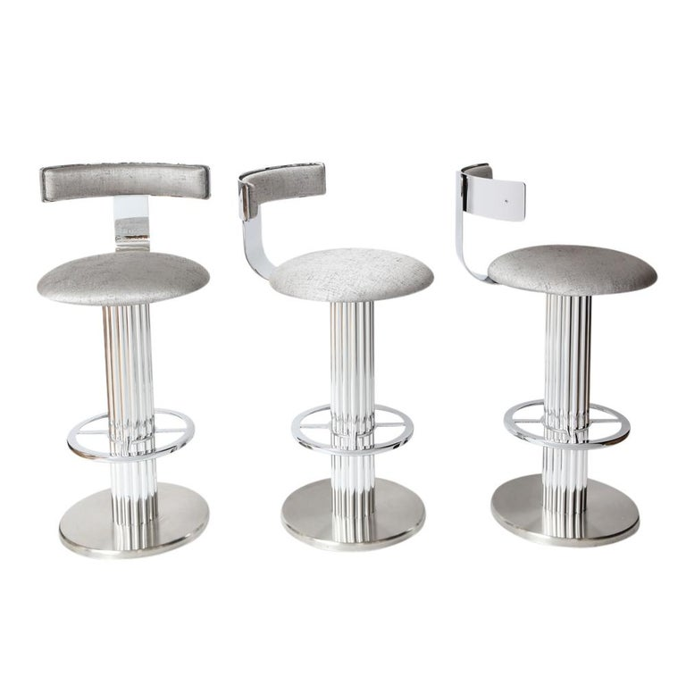 Bar stools by Designs for Leisure, chrome steel, swivel. Set of three heavy swivel barstools with high polished steel backrests and foot rests, polished aluminum reeded columns and brushed steel bases. Re-upholstered in a medium weight silver cotton