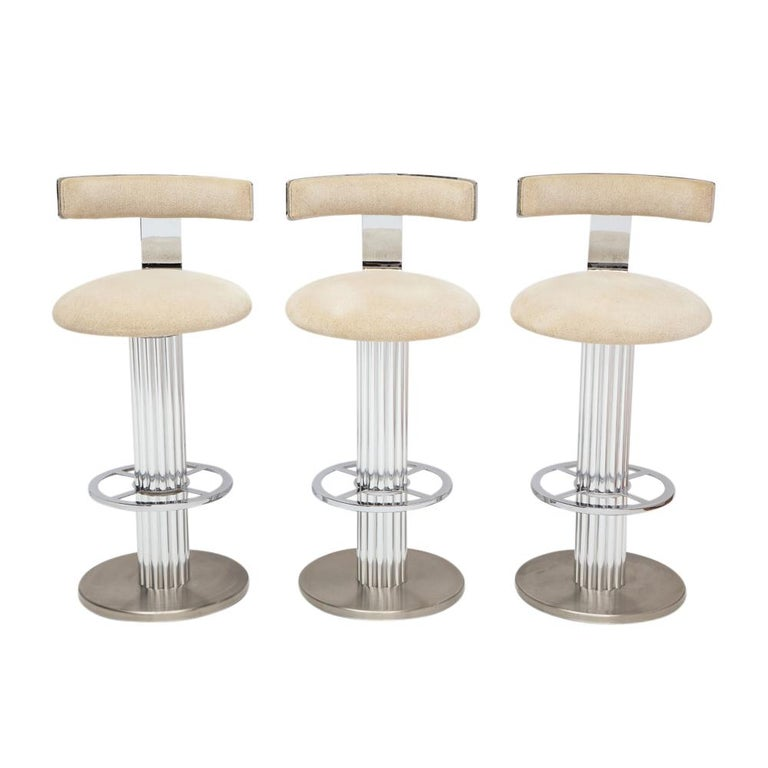 Bar stools by Designs for Leisure, nickeled steel, chrome. Set of three quality built and heavy swivel barstools (68 lbs each) with high polished steel backrests and foot rests, polished aluminum reeded columns and brushed steel bases. The seats and
