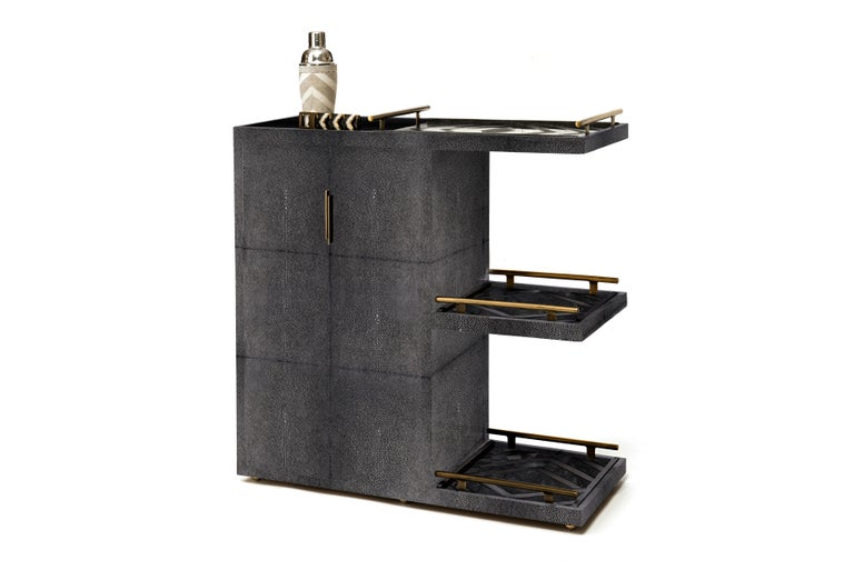 TheKifu Paris bar trolley in cream shagreen with bronze-patina brass details is a luxurious accent piece for any living space. This piece can be easily moved on invisible wheels and comes with three removable trays, in zig zag black shagreen/shell.
