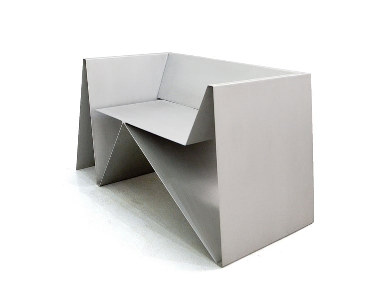 The Baralho armchair is a design by Flavio Franco. In this exquisite armchair the brushed aluminum folds in several directions, remembering a deck of cards (or a
