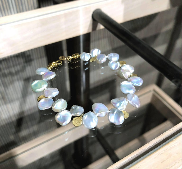 One of a Kind Bracelet handcrafted by award-winning jewelry artist Barbara Heinrich in 18k yellow gold featuring twenty-one lustrous silver blue keshi pearls accented with assorted 18k gold petal and bead charm elements. Stamped and hallmarked.
