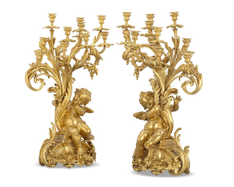 This rare and dramatic pair of Napoleon III gilt bronze candelabra were expertly cast and designed by the celebrated French bronzeur Ferdinand Barbedienne. Masterfully crafted, the candelabra are exemplary of the Rococo aesthetic. Organic swirls and
