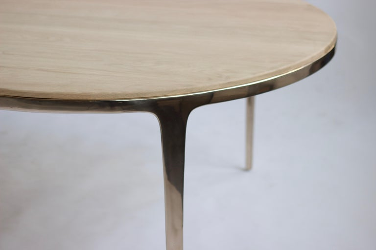 Designed by Daniel Barbera, the 'Bronze' table is a Minimalist oval table consisting of Classic geometry on the exterior merged with organic flowing underside. The four legged sandcast solid bronze base is hand finished to a smooth mirror polish,