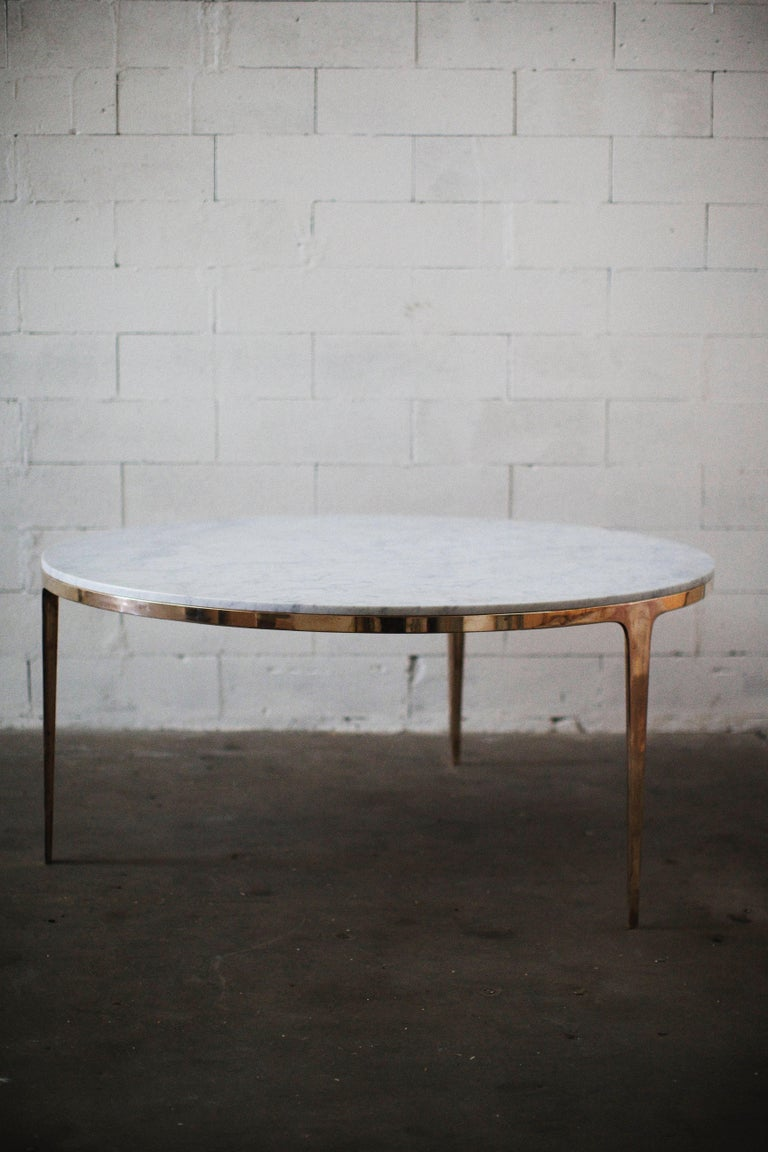 Designed by Daniel Barbera, the 'Bronze' table is a Minimalist round table consisting of Classic geometry on the exterior merged with organic flowing underside. The three legged cast solid bronze base is hand finished to a smooth mirror polish, with