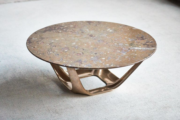 Designed by Daniel Barbera, the Heron coffee table, is a muscular sandcast solid bronze base with four organic forms rising from the base to support the top. The form is hand finished to a smooth mirror polish, with the option of a satin or