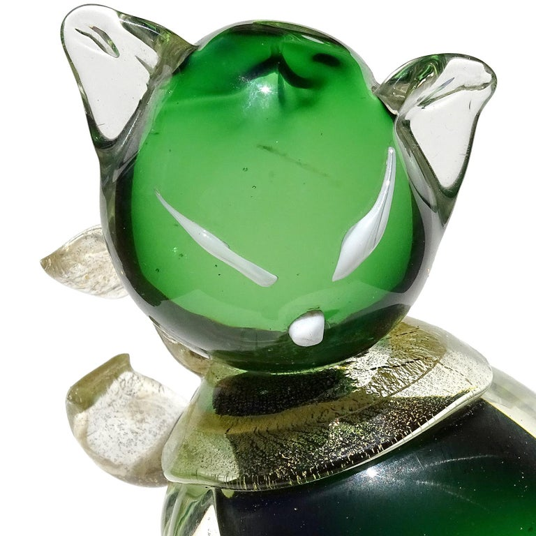 Beautiful Murano hand blown Sommerso green and gold flecks Italian art glass kitty cat sculpture on round base. Attributed to designer Alfredo Barbini. The piece has a gold leaf bow around its neck, gold tail and white eyes and nose. Stands on a