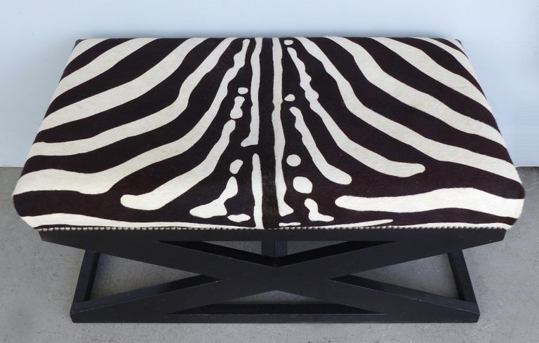 Offered for sale is a zebra print upholstered ottoman in the