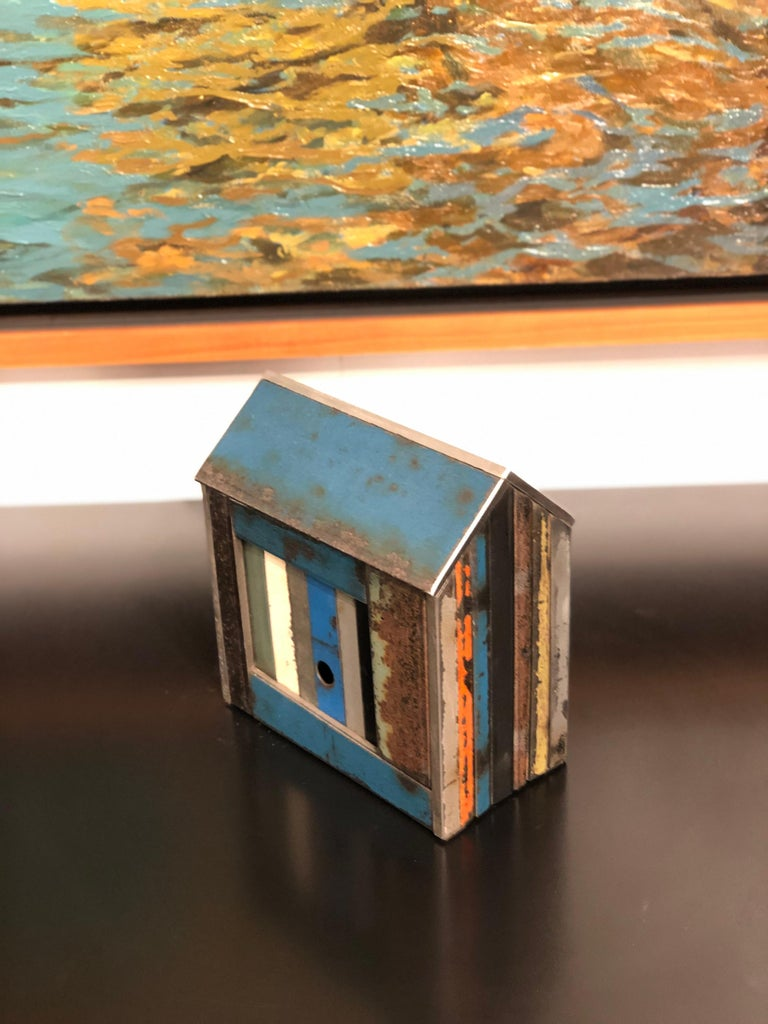 This is a welded steel sculpture made by furniture creator Jim Rose. It is created from salvaged steel panels left over from his larger projects. These sculptures reference traditional American Folk Art barn house models or bird houses. This