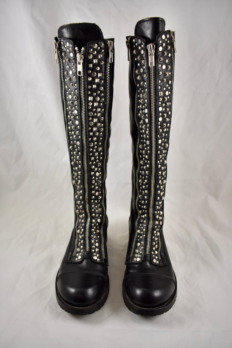 Barneys New York studded black leather zippered lug sole biker boots in original box. Made in Italy.  Triple working zippers and studding make this pair of biker boots unique. Knee high with a box toe, stacked wood heel and rubber lug soles.   Size: