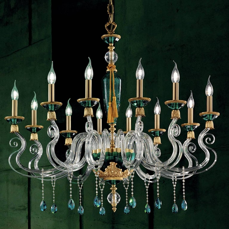 This captivating glass chandelier is inspired by the highly ornate Baroque style. This design has a central body with a green cylindrical element embellished with a golden rope and a gold-trimmed green base from which 12 clear, glass arms extend