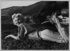 Sweet and laughing Filmstar Marilyn Monroe is laying on the green, 1954