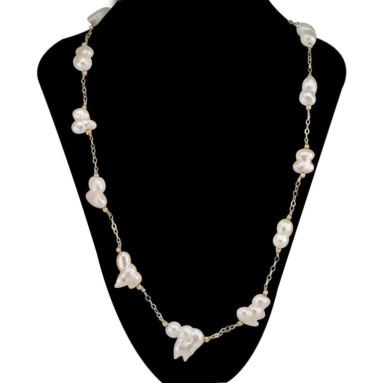 """Baroque cultured freshwater pearl and gold long necklace.  DETAILS:  PEARLS:  fifteen cultured freshwater pearls measuring approximately 20 mm X 13 mm overall.  METAL:  14-karat yellow gold.  MEASUREMENTS:  34"""" (86.36 cm) long overall.  CONDITION:"""