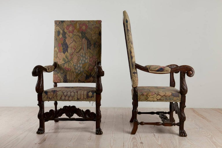 Swedish Baroque historic revival armchairs with paw feet, a pair, oak and tapestry upholstery, origin Sweden, circa 1890  The padded, arms carved with leaves, the front stretcher elaborately carved with arching scrolls and leaves meeting at