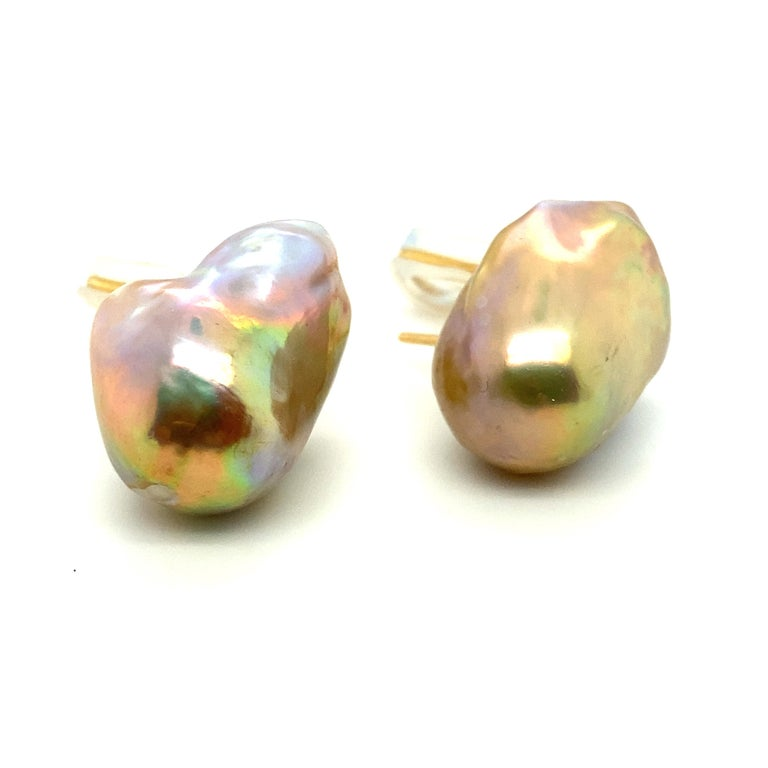 This pair of earrings is composed of two baroque pearls with a beautiful, multicolor 'rainbow' sheen ranging from purple-pinks to green to golden yellows to almost reddish undertones.  The pearls are well matched for baroques; they measure