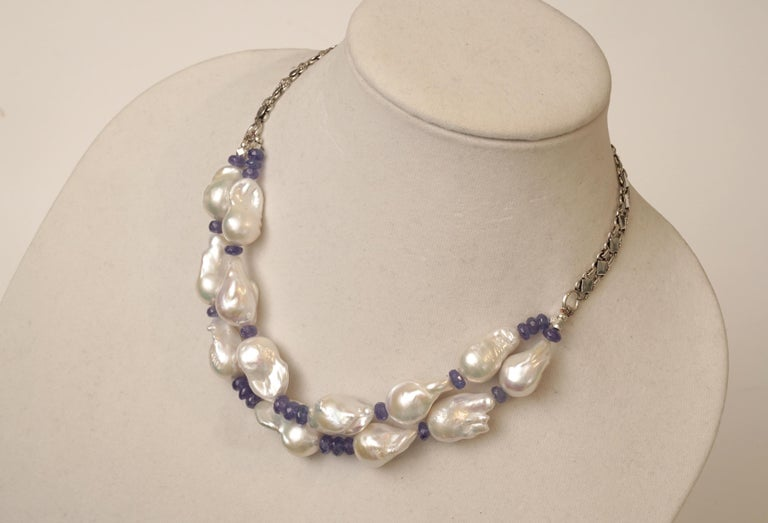 A double line of lovely baroque white pearls with excellent luster strung with faceted Tanzanite beads and sterling silver along the back.  By Deborah Lockhart Phillips.  The length can be adjusted at the back and length runs from 18 - 20 inches.