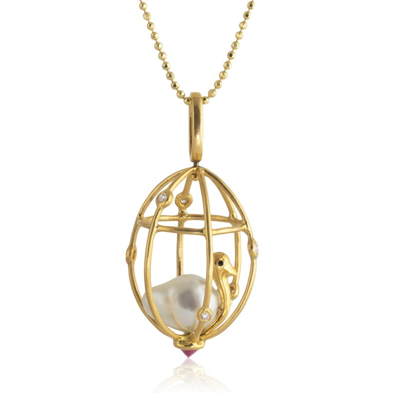 Perched inside this 18k diamond studded cage is a delicate bird; its body made from a 12mm x 9mm Baroque pearl, black diamond eyes decorating its golden body. The pendant features a reverse set .30 carat ruby at the bottom of the cage and swirls in