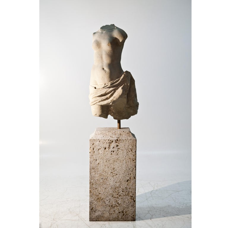 Baroque torso of a female figure made of sandstone mounted on a high pedestal. The sculpture has a beautiful patina and is life-sized.