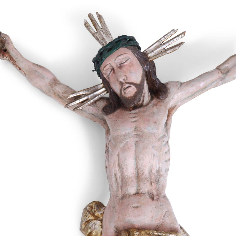 Baroque painted sculpture of crucified Jesus with gilt loincloth.