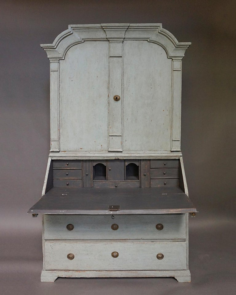 Period baroque secretary, Sweden circa 1820, in two sections. The upper library section has a bold arched cornice over double doors. The interior has three fixed shelves, the top one shaped and notched. The lower section has a fitted interior behind