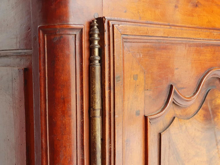 Long Baroque sideboard in solid walnut, Provence, 1730s.  Laterally flared, bent legs that end in volutes. A profiled frame, decorated with a carved rocaille in the middle. Two pairs of doors with profiled panelled doors and wide door hinges.