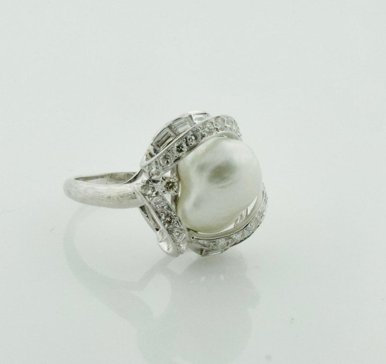 Baroque South Sea Pearl and Diamond Ring in White Gold Circa 1960's One Baroque South Sea Pearl Twenty Eight Round Brilliant Cut Diamonds Weighing ..85 Carats Approximately [GH VVS VS] Ten Baguette Cut Diamonds Weighing .50 Carats Approximately