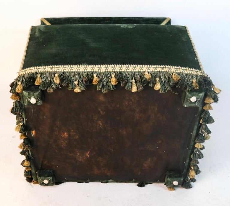 Dog house upholstered with green velvet and green and cream fringe. Hinged top revealing green pillow within.