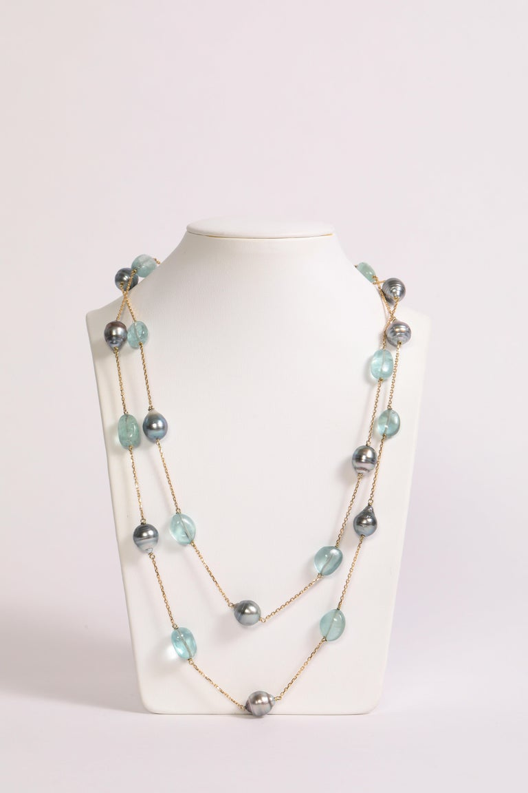 Light blue and grey colored long necklace. Twelve Tahiti pearls, eleven aquamarine tumbles, 18K yellow gold. Created by Marion Jeantet.  Total weight: 44.12grs French assay mark Price without local taxes Aquamarine's weight: 80.08 carats