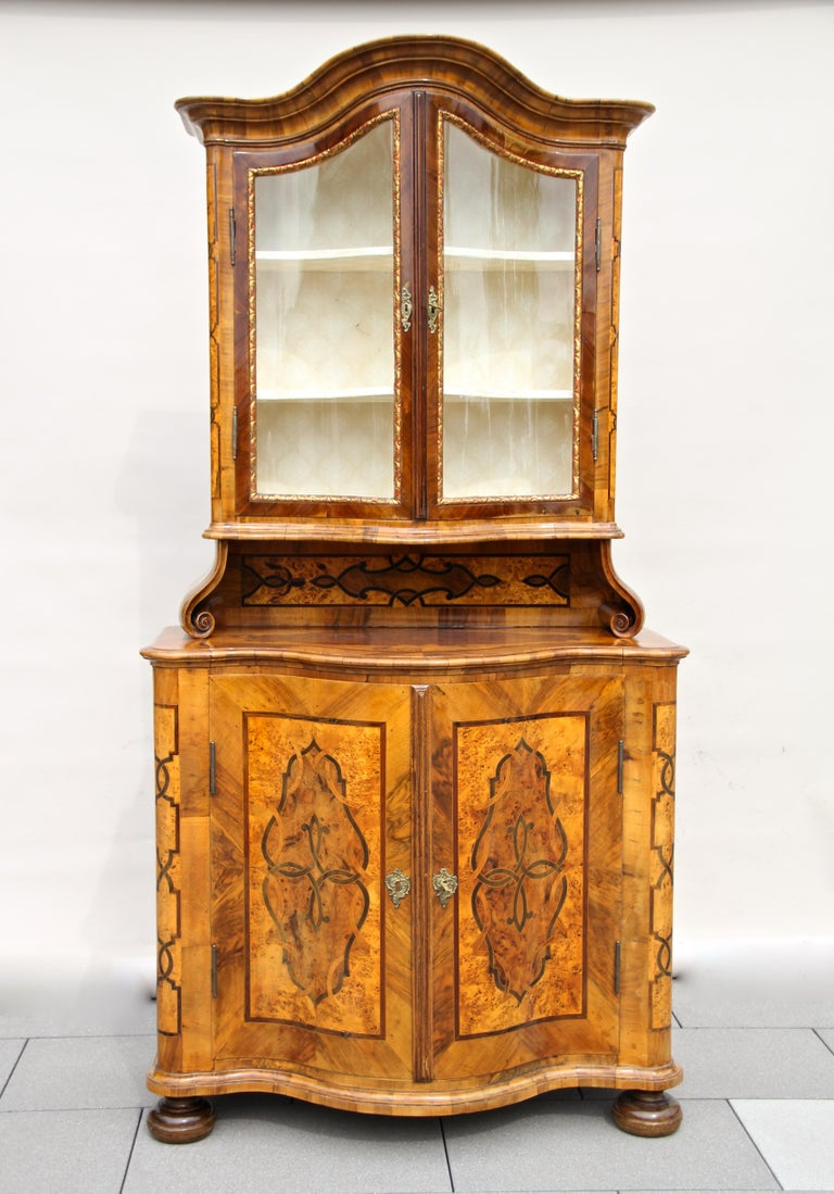 Stunning baroque vitrine cabinet out of Austria from the 18th century, circa 1760. This masterful inlayed cabinet was restored about 25 years ago and is in a nice ready-to-use condition. Fantastic veneer like burr walnut, nut wood, maple, birds eye